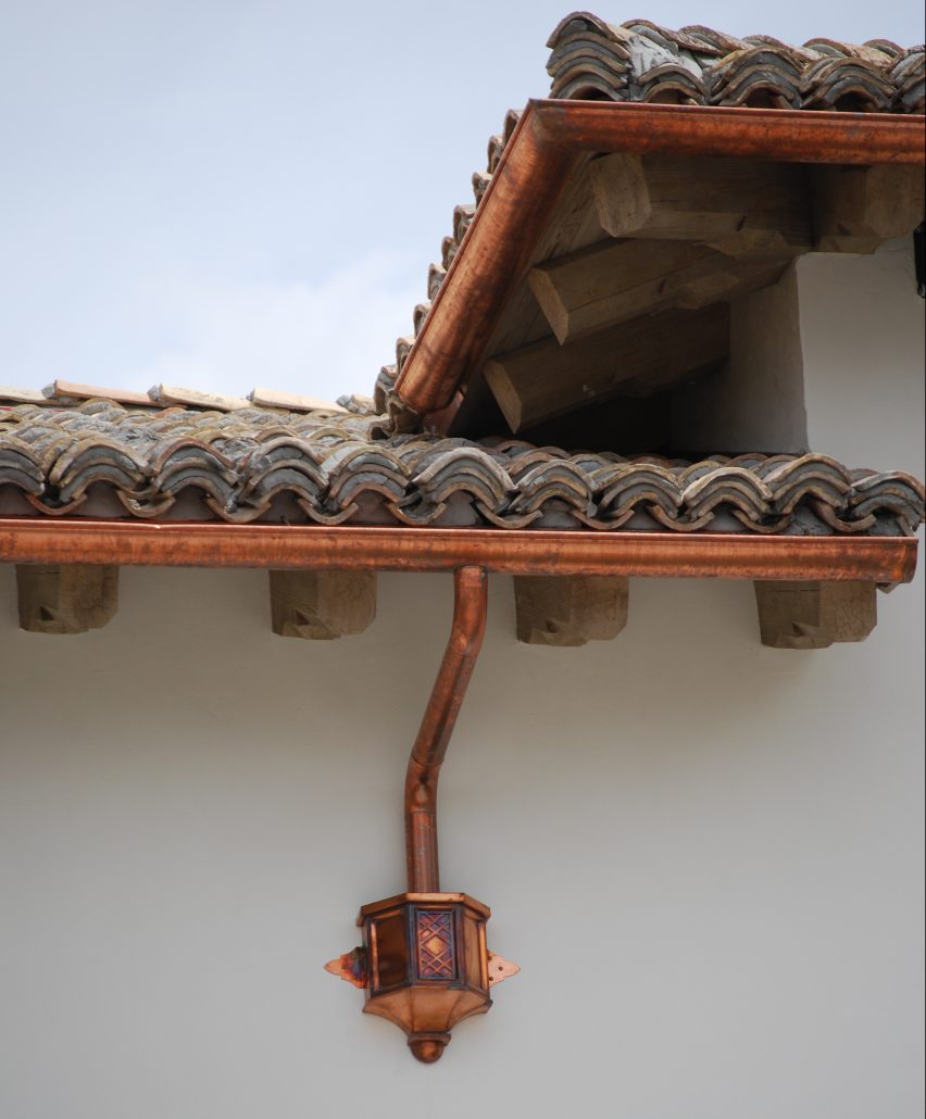 copper designer gutters and downspout on tile roofed home