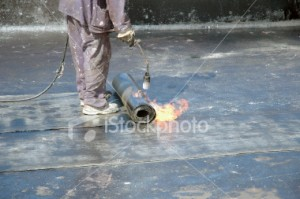 Roofer applying heat seal to flat roof installation