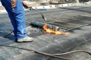 Roofer hot sealing an EPDM flat roof