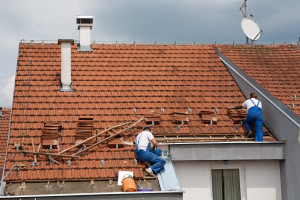 two men working on a damaged spanish tile roof