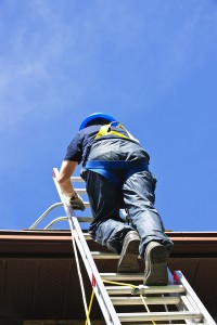 Professional roofer with safety equipment climbing ladder