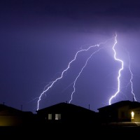 lightning display over roofs of three houses in southwestern united states