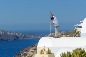 man saving energy by painting a whitewashed roof overlooking the sea in sunny Greece