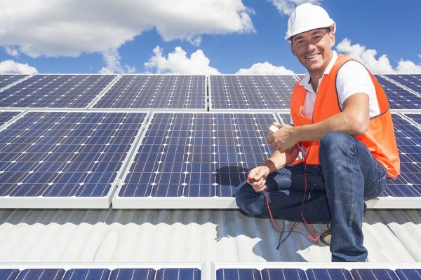 Solar panel technician on roof with solar panels