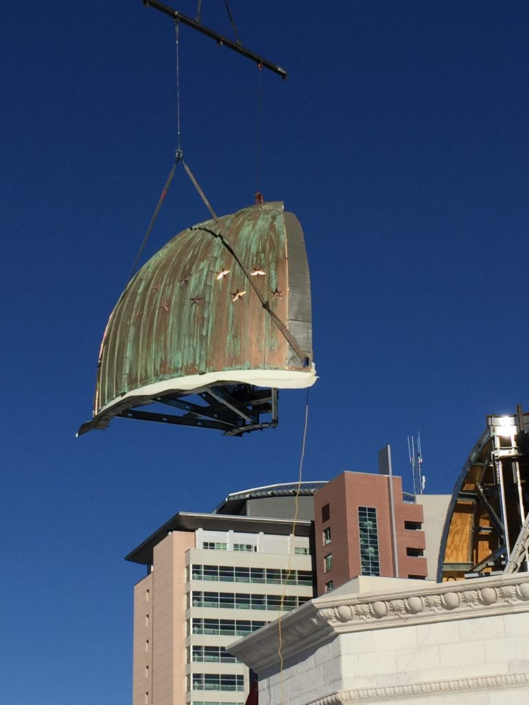 A quarter piece of copper cupola dome being installed