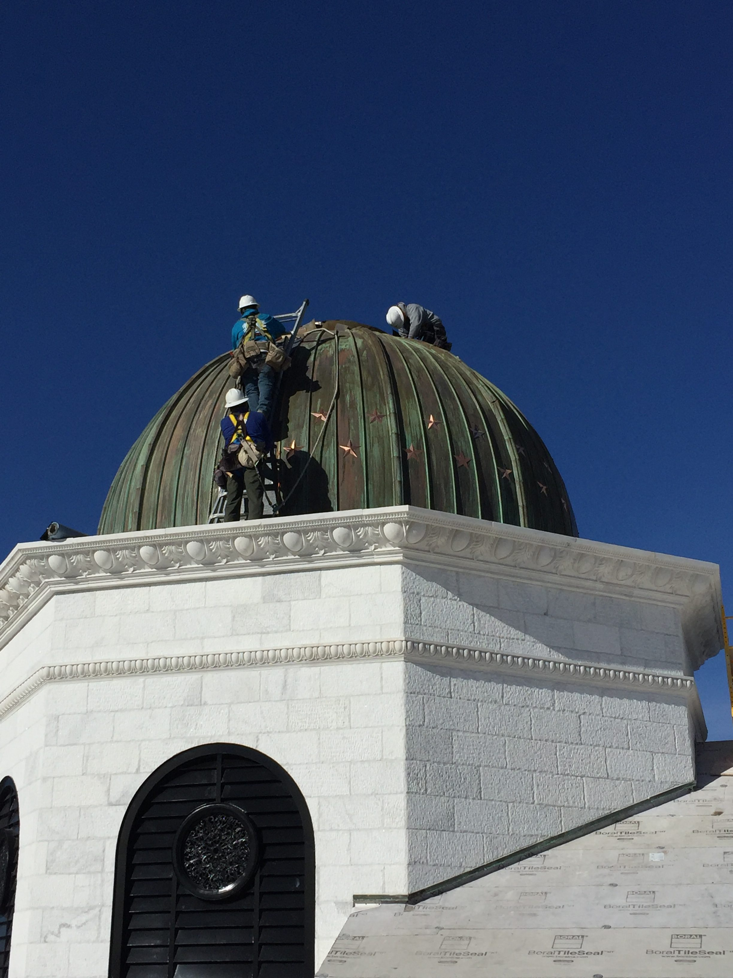 three roofers completing work on top of a copper cupola dome on the roof of a new building