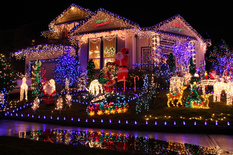 home decorated with christmas lights on the roof and yard decorations