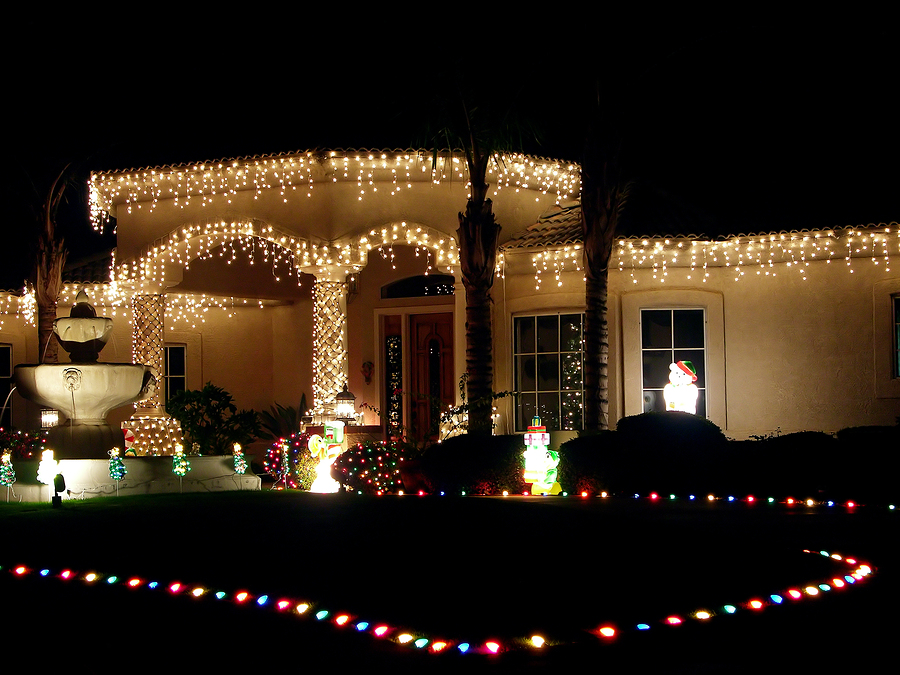 fountain and christmas lit house including lights defining driveway.