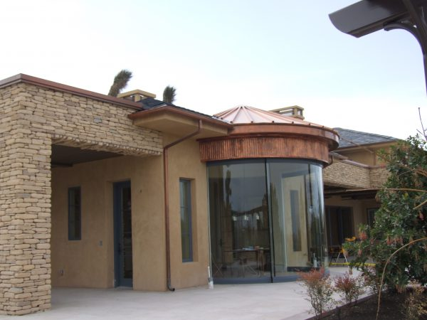 copper rain gutter on wall of luxuyr home with new copper roofing