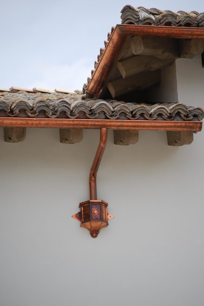 copper rain gutter on tile roof home