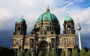 Berliner Dom showing bright patina copper domes and Fernsehturm in front of blue sky