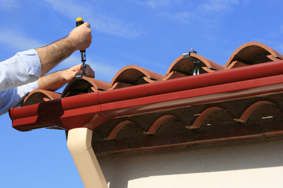Man repairing rain gutter system on a house