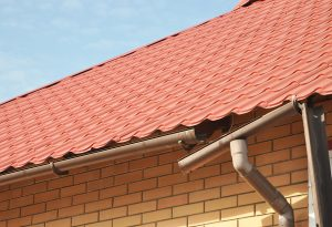 Broken rain gutter on metal tile roof in need of repairs