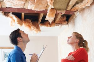 Builder And Client Inspecting Roof Damage Together