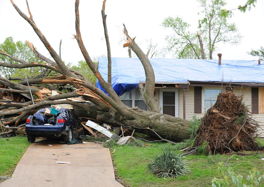 Damaged home with tarp-covered roof after tornadoes hit