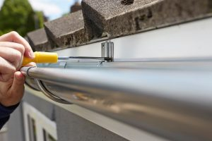 Close Up Of Man Replacing Roof Rain Guttering On Exterior Of House