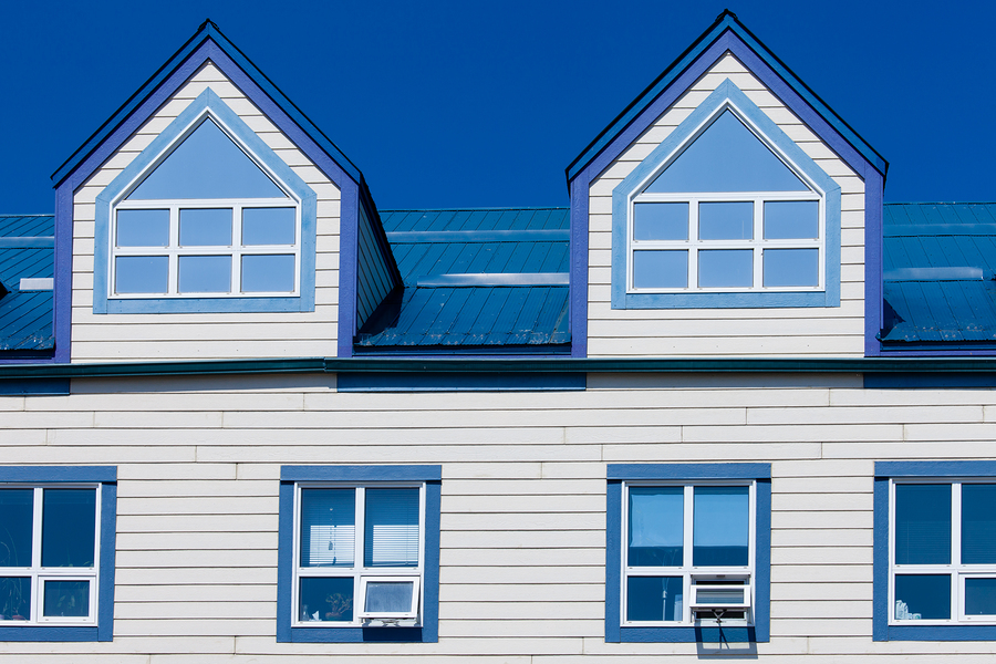 Exterior detail of frame building upper story windows and two dormers in blue metal roof