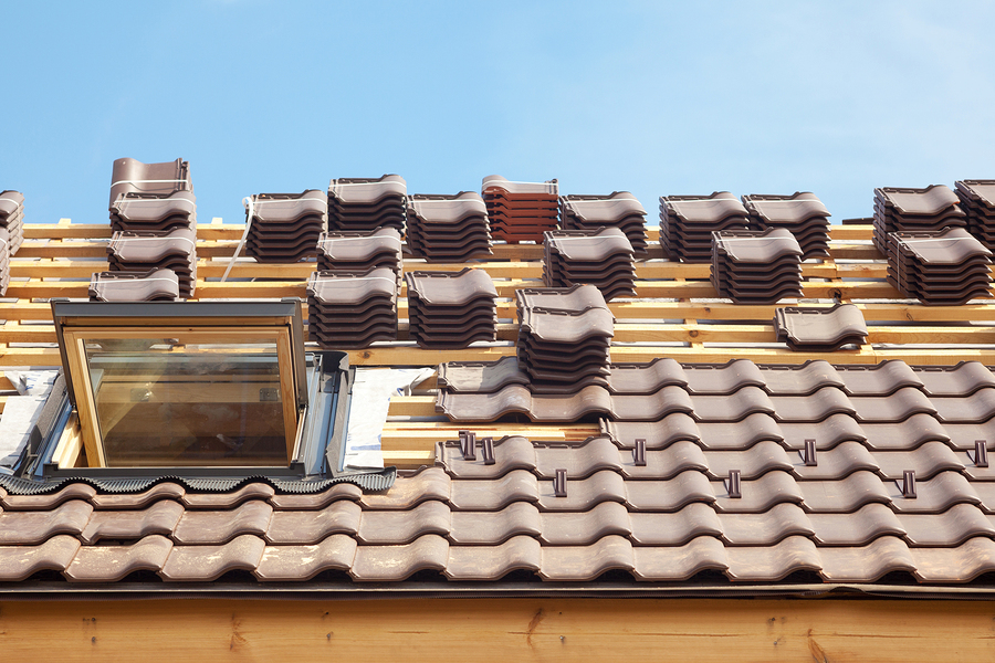 House under construction. Roofing tiles with open skylight