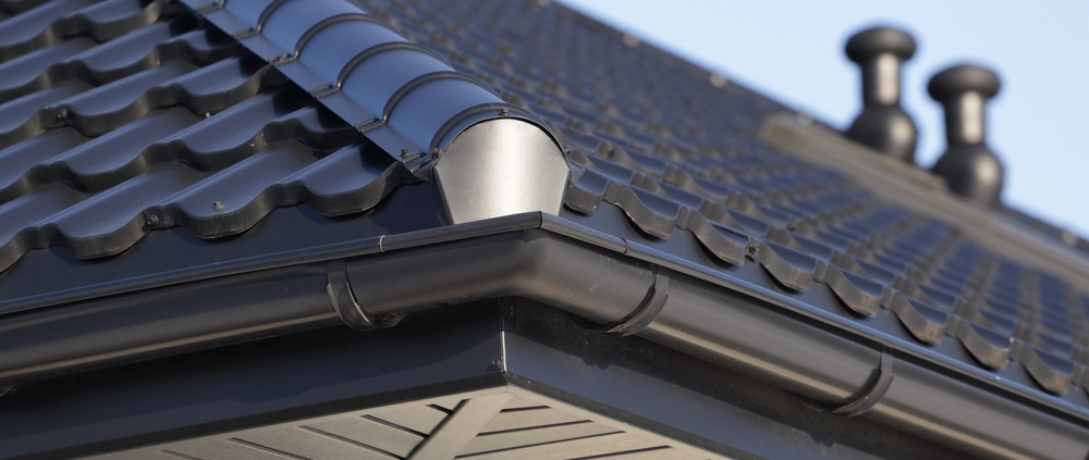 Corner of new zinc roof and zinc rain gutters on a house