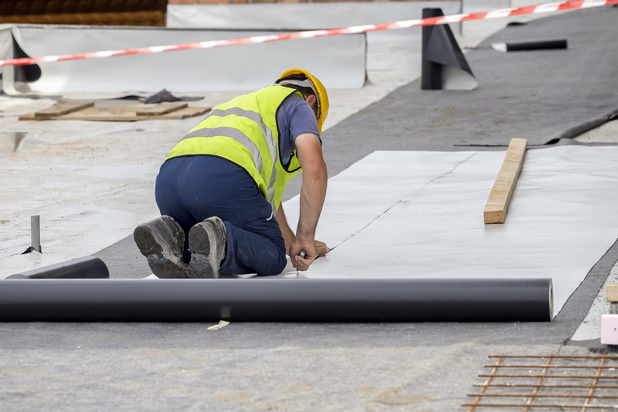 PVC flat roof installation with roofer in hard hat cutting the PVC waterproofing material