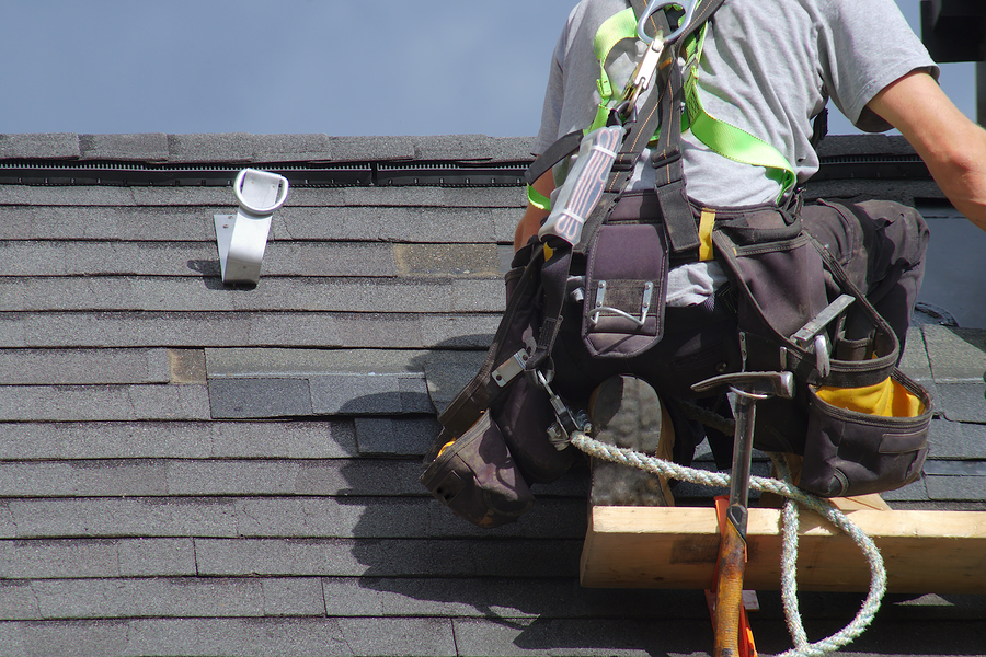 roofer with safety equipment and PPE repairing an asphalt roof
