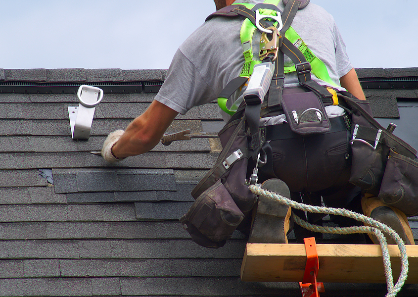 Roofer with personal fall arrest safety system working on a new roof installation