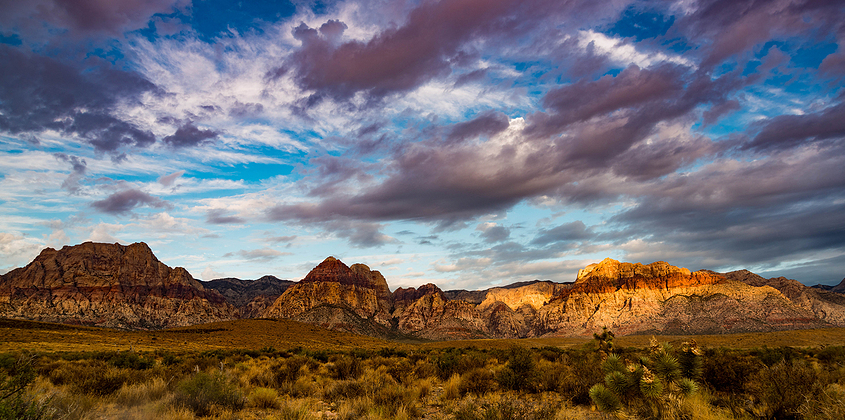 clouds and ray of sun over the red rock mountains