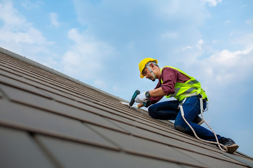 Roofer on rooftop repairing shingles